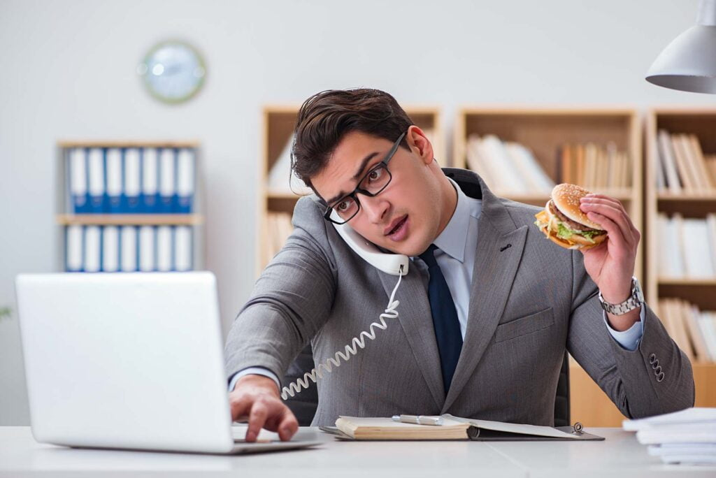 man eating burger in front of laptop